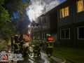 Ein Feuer in der Flüchlingsunterkunft an der Großen Horst 2 sorgte am Samstagabend für Aufregung. Zwei Wohncontainer brannten komplett aus und zwei Familien verloren ihr Hab und Gut. Sie mussten durch die Feuerwehr betreut werden. Löschversuche der Bewohner mit unzähligen Feuerlöschern blieben erfolglos. Durch den Einsatz von mehreren Rohren im Innen- und Außenangriff gelang es aber der Feuerwehr den Brand zu bekämpfen. Foto: Dominick Waldeck